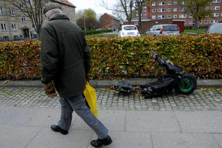 COPENHAGEN  DENMARK_ 사람이 도난당한 모터 자전거에서 바퀴를 제거했습니다. 2014 년 10 월 27 일 에디토리얼