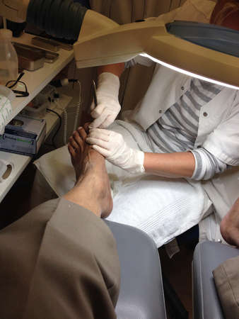 treating: COPENHAGENDENMARK_Podiatist or chiropodist treating foot of diabetes patient at podiatist clinic, 13 November 2014