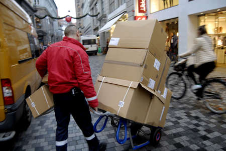mail man: COPENHAGENDENMARK_  Danish mail man with parcels  for delivery         05 December   2014
