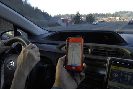 bellevue: Seattle. Washington state. USA   Driver using map quest at iphone to find route in sSeattle havey trafic             14 December   2014.