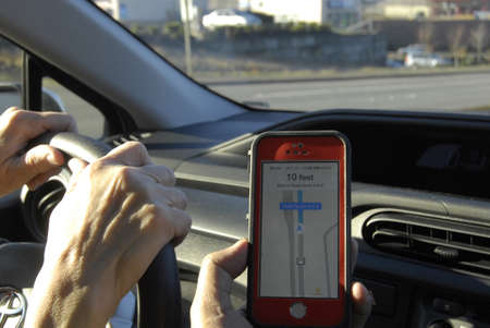 trafic: Seattle. Washington state. USA   Driver using map quest at iphone to find route in sSeattle havey trafic             14 December   2014.