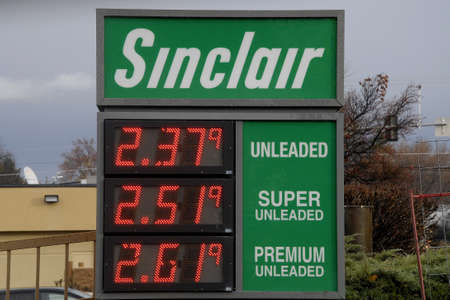 cheaper: Lewiston . Idaho state. USA Gas price fall today gasoline per gallon is cheaper then yesterday today price tag at Sinclair and Chevron gas station in Lewiston valley.               19 December   2014.