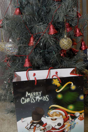 Lewiston . Idaho state. USA _Christmas presents under articial christmas tree Merry Christmas with santa figire bag              21 December   2014.