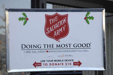 unfortunate: Lewiston . Idaho state. USA_male working valunteer ringin bells and open door for christams shoppers at mall ,male rig bell for christmas chairty for Salvation army to help unfortunate for christmas help                 22 December   2014.