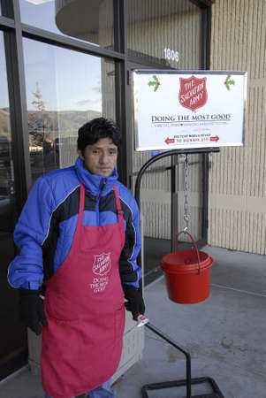 Lewiston . Idaho state. USA_male working valunteer ringin bells and open door for christams shoppers at mall ,male rig bell for christmas chairty for Salvation army to help unfortunate for christmas help                 22 December   2014.