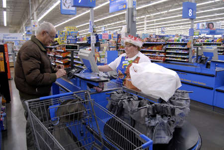 Clarkston. Washington state. USA_Americans shopping on christmas eve  at Walmar store and cashier wearing santa claus hat in christmas celebration mode                24 December   2014. Editorial
