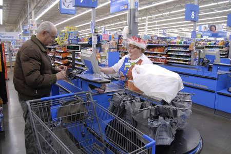 walmart: Clarkston. El estado de Washington. USA_Americans compras en la v�spera de Navidad en la tienda Walmar y cajero llevaba sombrero de santa claus en navidad celebraci�n modo de 24 diciembre de 2014.