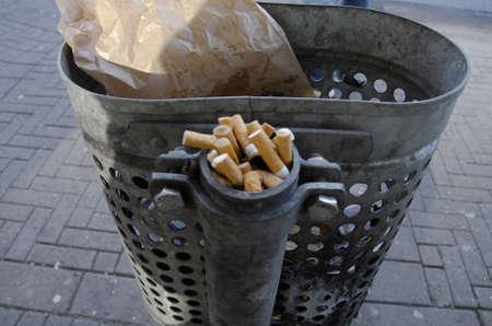 waste basket: COPENHAGENDENMARK. 26 February 2015 -     Left over cigarettes on bust stop waste basket Editorial