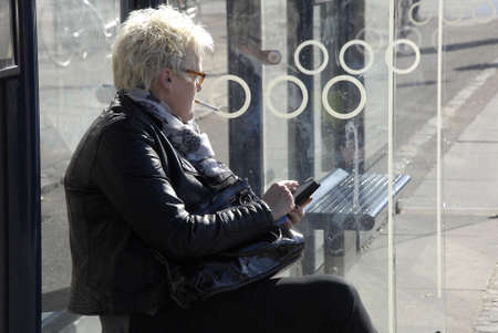moder: Copenhagen-Denamrk ,  09 March  2015_ Old female using iphone moder technilogy fr communication while waiting for transportation at bus stop in city today on monday Editorial