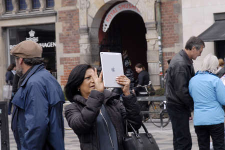 francis dean: .Copenhagen.Denamrk _25 April 2015_ Female travlers taking photo by ipad on stroget Editorial