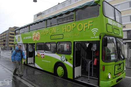 tourists stop: COPENHAGENDENMARK. 26 April 2015  Foreign travelers getting in Hop on -hop off sightweeing green line bus at Christianshavn stop today on sunday
