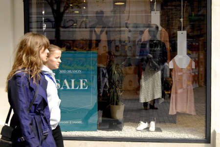 adds: COPENHAGENDENMARK. 30 April 2015    _Shopphers walk by store adds with Mid season sale on kobmagerkade today