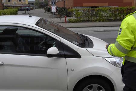 francis dean: Copenhagen Denamrk _05 May 2015_     Parking inspector gives parking ticket on alleen Editorial