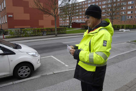parking ticket: Copenhagen Denamrk _05 May 2015_     Parking inspector gives parking ticket on alleen Editorial