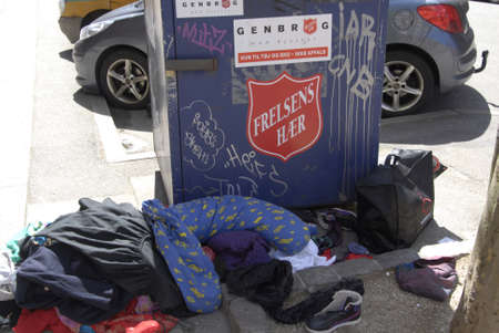 francis dean: Copenhagen Denamrk _14 May 2015_  Peopple leave old cloths at salvation army chairty container infron 2nd hands sale store on amager