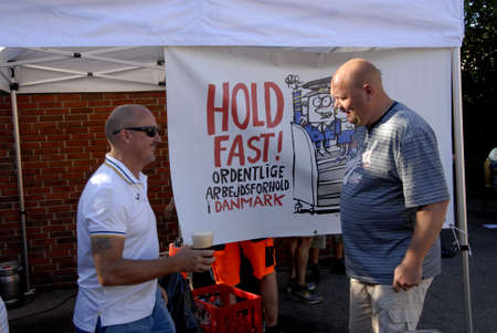 favour: COPENAHGEN DENMARK 01 July  2015_  3ftrade union member celebrate and holding party  with beer sausage and dance danish labour court rulling in favour of danish trade union and agianst Ireish Ryanair compnay ,ryainair must obey danish workin and wages ru