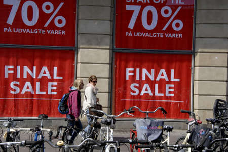 nord: CopenhagenDenmark 21 July 2015_Shoppers walk by final 70% disocunt  sale sign in windows at Magasin du nord department store