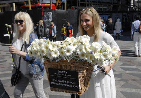 sommer: CopenhagenDenmark 03 August  2015_ Young blonde female distibute daisy flowers to promte Marc Jacobs new perfume Daisy on sale from today in Copenhagen, Stroke fountain decorate with daisy flowers to remind shoppers and tourists Marc Jacobs New daisy pe