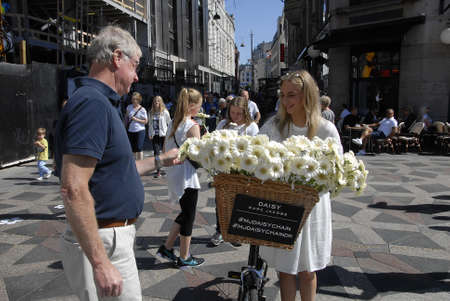 marc: CopenhagenDenmark 03 August  2015_ Young blonde female distibute daisy flowers to promte Marc Jacobs new perfume Daisy on sale from today in Copenhagen, Stroke fountain decorate with daisy flowers to remind shoppers and tourists Marc Jacobs New daisy pe