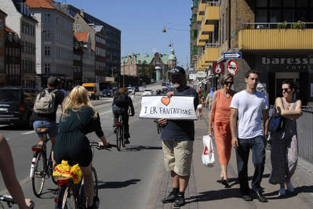 seeks: CopenhagenDenmark 13 August  2015_Danish man seeks hugs  with banner your are fantastic  to by passers at christianhavn canal bridge Editorial