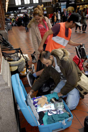 cruz roja: CopenhagenDenmark 11 September   2015_Syrian refugee family arrives from Germany to Copenhagen with small kids and Red cross vakuteer from muslim background are in process to help family to find them suitable item for their use at Copenhagen Central tri