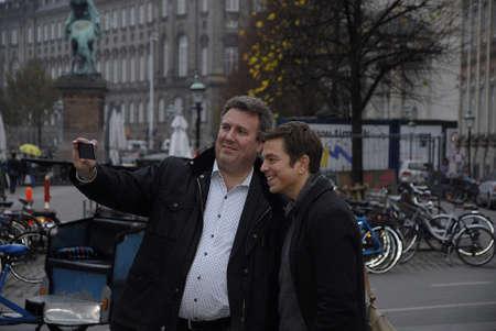 danmark: CopenhagenDenmark _ 02 November  2015_ Danmark radios national television broadcasting Eruepean Union Correpondent Ole Ryborg and Niel Kvale talking slefie  in Copenhagen amager torv stroeget  Denmark