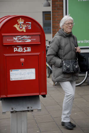post box: Copenhagen Kastrup.Denmark 13 March  2016 _people walk by demages royal post box one now called Postnord at taarmby torv