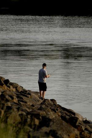 unites: Lewiston Idaho USA- 31 May 2016_Lewiston male catches fish in Snake river in temperature  100 degree fahrentheit  over looking Clarkston Washington                _