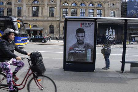 tourists stop: Copenhagen  Denmark. 04 July 2016_Billboard with David Robert Joseph Beckham add for No.1 worldwide in premium men,s skineare at bus stop in Copenhagen Denmark .