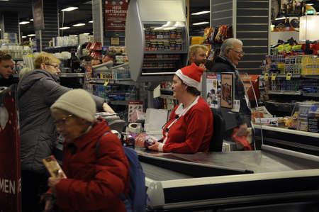 chrstmas: Copenhagen  Denmark_  23Th.December 2016 -   MErry christmas sign  (gl?delig Jul) and christmas shoppers in food store .