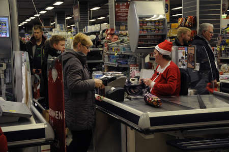 fakta: Copenhagen  Denmark_  23Th.December 2016 -   MErry christmas sign  and christmas shoppers in food store .
