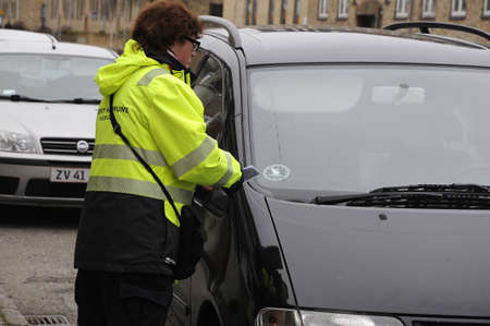 Kastrup_ Copenhagen_Denmark _28 .March  2017_ Famel parking inspector from Taarnby council writing parking fine ticket for over parking timimg here on Kastruplundgade is allow 2 hours free parking for near residential area Alleen and Kastruplundgade. Editoriali