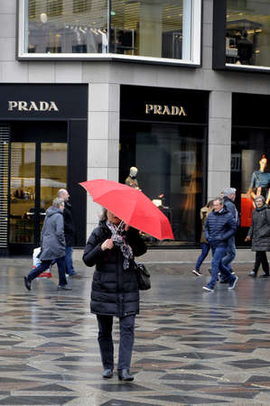 prada: Copenhagen  Denamrk 29 March 2017 -Shoppers and tourists with under umbrellas due to rainy weather day in danish capital and rest of the country. Editorial