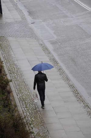 Kastrup_ Copenhagen_Denmark _15.April 2017_Male under umbrella wet and rainy day in Denmark .