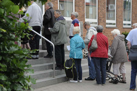 finanse: Copenhagen Denmark - 14 June 2017.  Danish senior citizen standing in line to buy annual picnic ticket from council for annual lunch party.