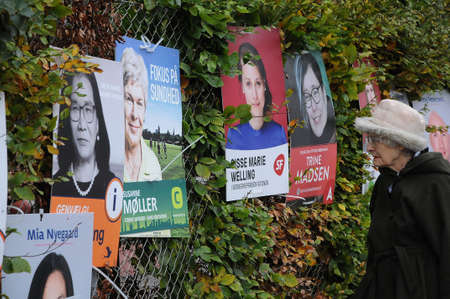 Copenhagen Denmark - 02 November  2017.     Eldlery female study county and council elections playcards by vaious danish political parties  caiddates here in danish capital dane will vote for county and council election in november 2017. Editorial