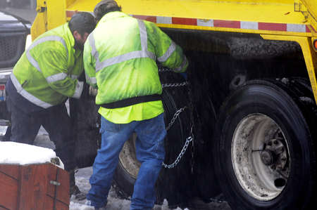 LEWISTON/IDAHO/USA 29.December  2017.  Disposal and  recyle men fisxing iran snow chains on tyres due to disposal recycling truck stuck in snow while heavy rain  in Lewiston, Idaho Standard-Bild - 114716711