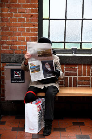 Copenhagen/Denmark 16.December 2018.  Female reading freign language news papers at main train tstion in Copenhagen Denmark . Editorial