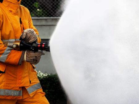 firefighter training., fireman using water and extinguisher to fighting with fire flame in an emergency situation Фото со стока