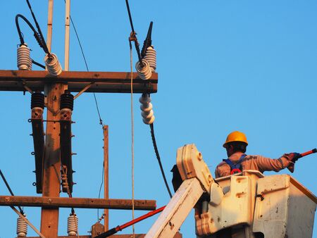 electrician man working at height and dangerous ,high voltage power line maintenance Foto de archivo