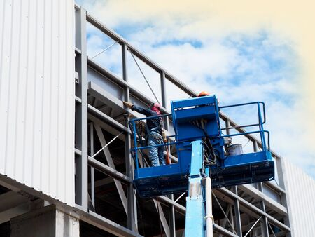 Construction worker at construction site using lifting boom machinery Stock Photo