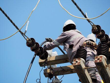 Elektriker, der in der Höhe arbeitet und gefährlich ist, Wartung von Hochspannungsleitungen