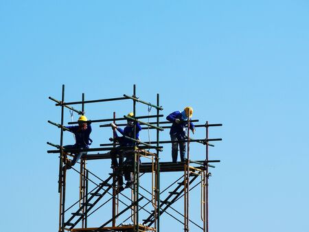 Construction workers working on scaffolding, Man Working on the Working at height with blue sky at construction site Stockfoto