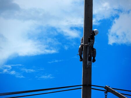 electrician man working at height and dangerous ,high voltage power line maintenance Banco de Imagens