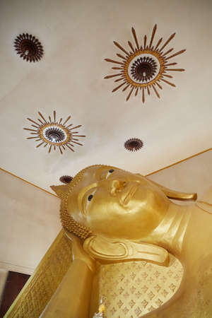 Reclining Buddha gold statue face. Bangkok, Thailand.