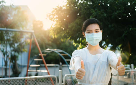 Beautiful Asian woman wearing a face mask smiling with a thumb up at outdoor ,To prevent the virus Covid-19 pandemic, stay safe and social distancing concept for protect from Corona virus, PM 2.5