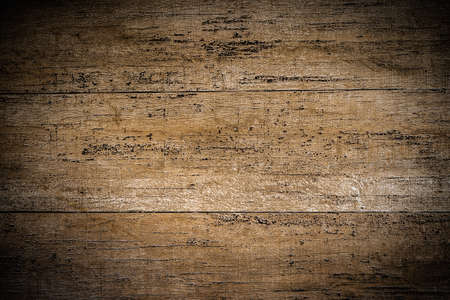Background close-up photos of the texture details of the dark brown wood grain background. Grunge and dirty style with a vignette in the corner of the image and bright spot in the middle .