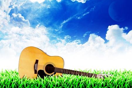 草のフィールドと曇り空背景: 草の上のギター 写真素材