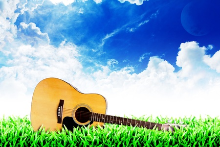 country music: Grass field and cloudy sky background : guitar on the grass