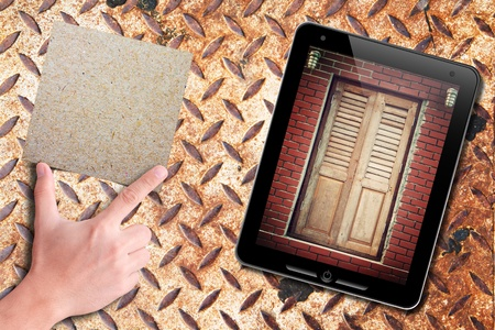dictatorial: touch pad with old door background and recycle paper on hand: grunge rusty plate  Stock Photo